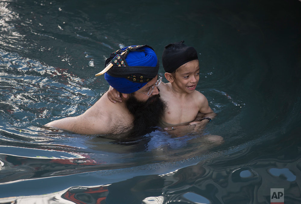 A Sikh pilgrim takes a holy bath with his child during a religious festival in Hasan Abdal near Islamabad in Pakistan, Friday, April 14, 2017. AP Photo/B.K. Bangash)