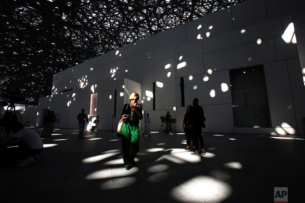 In this Monday, Nov. 6, 2017, photo, a journalist walks under the lights coming through of the dome at the Louvre Abu Dhabi, United Arab Emirates. The Louvre Abu Dhabi is preparing its grand opening _ unveiling its treasures to the world after a decade-long wait and questions over laborers' rights. The museum, which opens on Saturday to the public, encompasses work from both the East and West. (AP Photo/Kamran Jebreili)