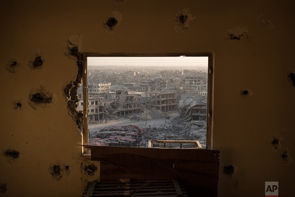 In this July 11, 2017 photo, destroyed buildings are framed by the window of a damaged hotel on the west side of Mosul, Iraq. Iraq???s U.S.-backed forces succeeded in wresting Mosul from the Islamic State group but at the cost of enormous destruction. The nearly 9-month fight culminated in a crescendo of devastation _ the blasting of the historic Old City to root out the militants??? final pockets. (AP Photo/Felipe Dana)
