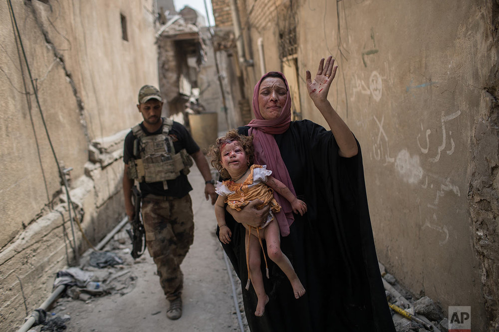 A woman carries an injured young girl as Iraqi forces continue their advance against Islamic State militants in the Old City of Mosul, Iraq, Monday, July 3, 2017. (AP Photo/Felipe Dana)