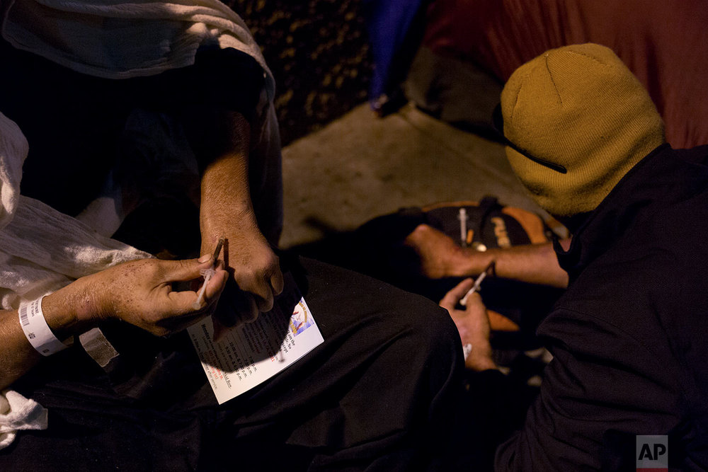 "Two homeless drug addicts inject themselves with heroin in the Skid Row area of downtown Los Angeles Monday, Nov. 6, 2017. The man on the right, who has been doing drugs everyday since January, said it was a nightmare trying to quit.  ""If we could stop, we would, you know. But you get sick."" the addict said. ""I have daughter now in Alabama. I just had a granddaughter I may never see."" (AP Photo/Jae C. Hong)"