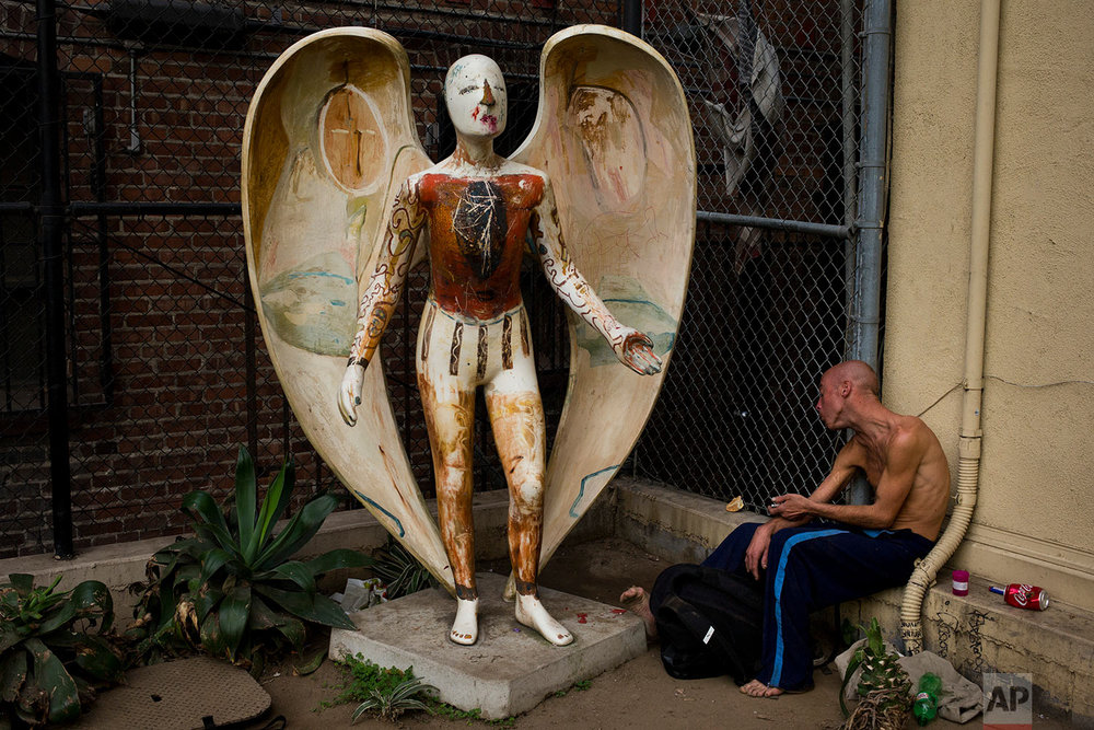 "Homeless drug addict Andrew Hudson, 33, reacts as he injects himself with heroin next to an angel statue Wednesday, Nov. 8, 2017, in the Skid Row area of downtown Los Angeles. ""It's miserable quitting, or trying - trying anything,"" said Hudson. (AP Photo/Jae C. Hong)"