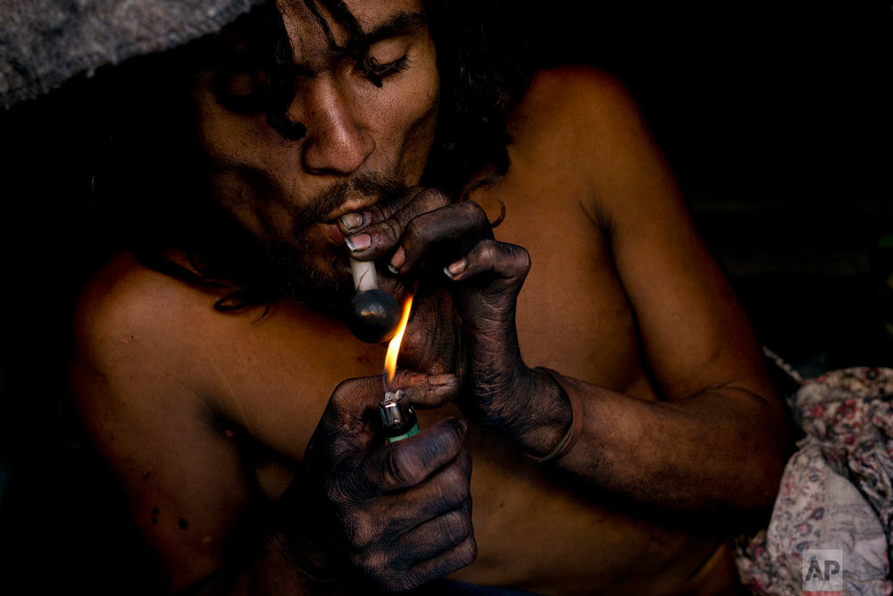 A homeless drug addict, who said his name is Barbie, smokes crystal meth in his tent Saturday, Nov. 4, 2017, in downtown Los Angeles. (AP Photo/Jae C. Hong)