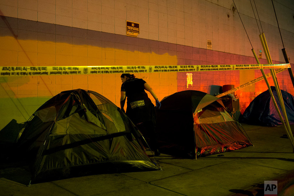 Los Angeles County Coroners investigator Kelli Blanchard looks around a tent where the body of 33-year-old homeless man Andrew Withrow was found Monday, Sept. 11, 2017, in the Skid Row are of downtown Los Angeles. (AP Photo/Jae C. Hong)