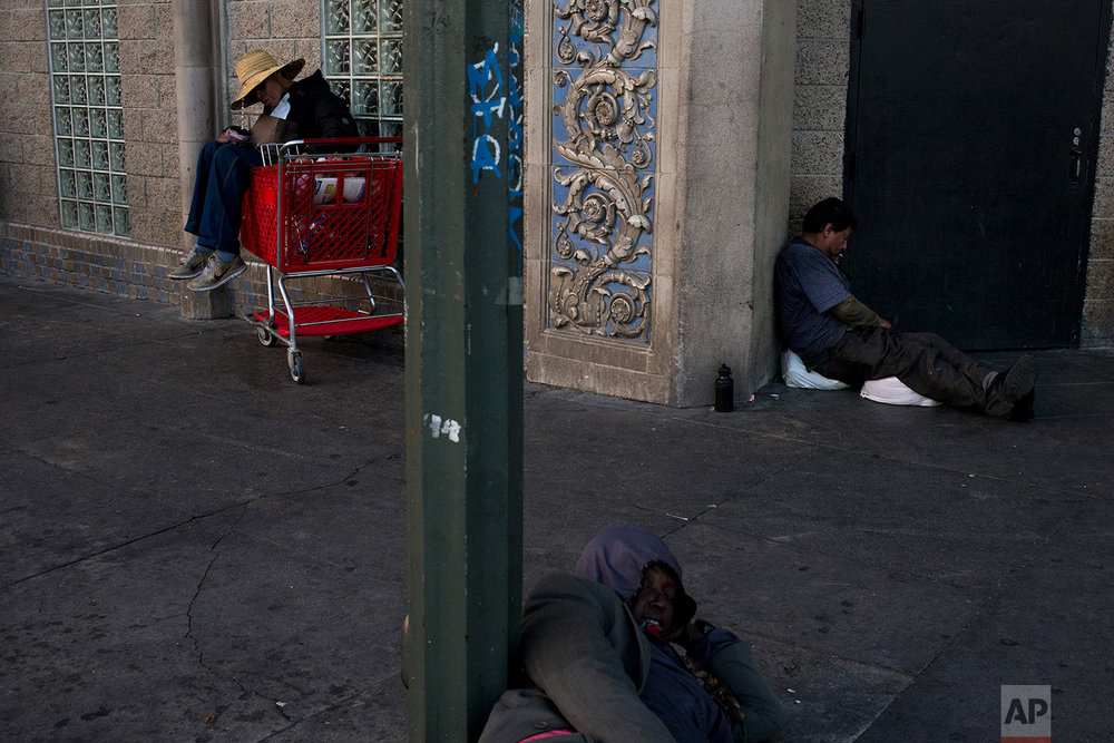 Three homeless people take a nap on a sidewalk in the Skid Row area of downtown Los Angeles Monday, Nov. 6, 2017. (AP Photo/Jae C. Hong)