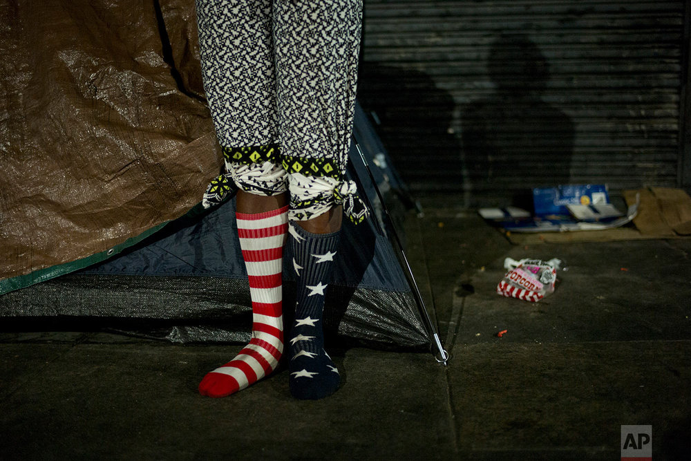 Wearing a pair of American flag socks, homeless Stafford Wilson, 48, stands in front of his tent while dancing to music Tuesday, Nov. 7, 2017, in the Skid Row area of downtown Los Angeles. (AP Photo/Jae C. Hong)