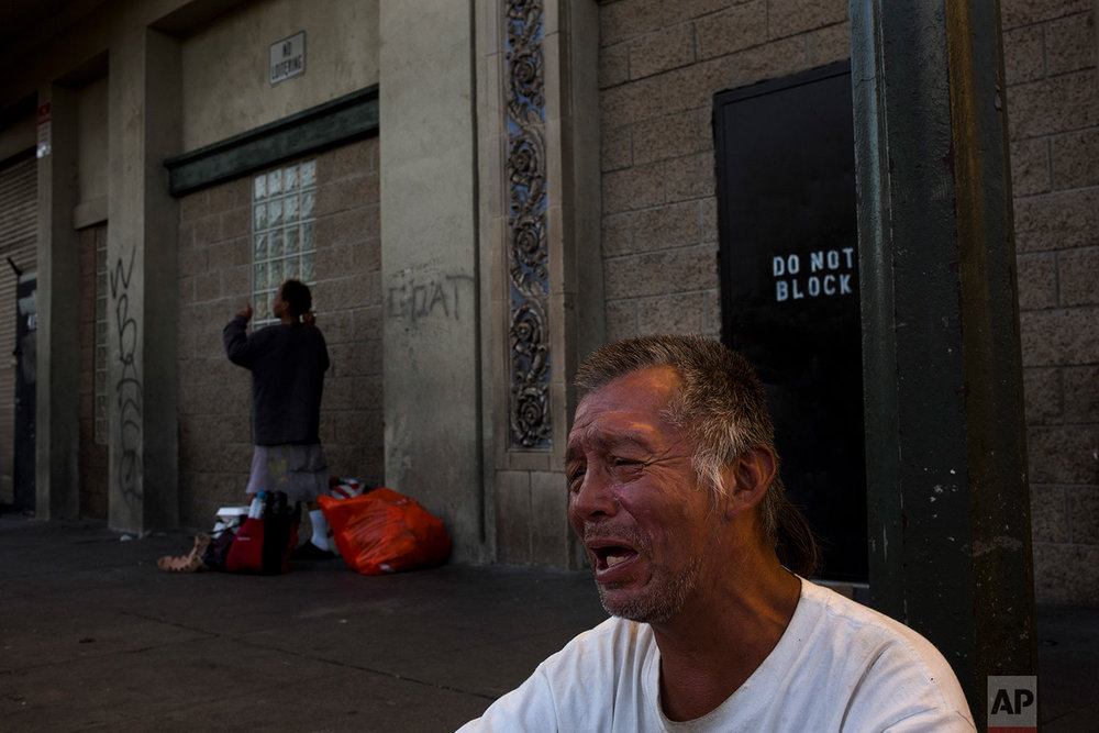 "Homeless man Jack Harten breaks down as he listens to gospel music while drinking beer on a sidewalk across the street from the Midnight Mission Wednesday, Nov. 22, 2017, in Los Angeles. Harten said he drinks about 12 cans of beer daily. ""I'm tired of drinking,"" he said, sobbing. Help exists, but too many turn to drugs to cope their problems. (AP Photo/Jae C. Hong)"