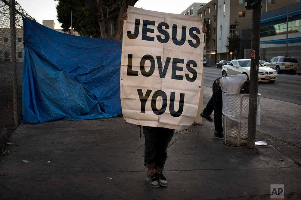 "Samuel Raymond, 50, holds up a banner saying ""Jesus Loves You"" on a sidewalk as a passing homeless man reaches into a trash can in search of anything of value Saturday, Nov. 4, 2017, in the Skid Row area of downtown Los Angeles. ""The Lord is my shelter,"" said Raymond, who has been homeless for nearly 20 years. (AP Photo/Jae C. Hong)"