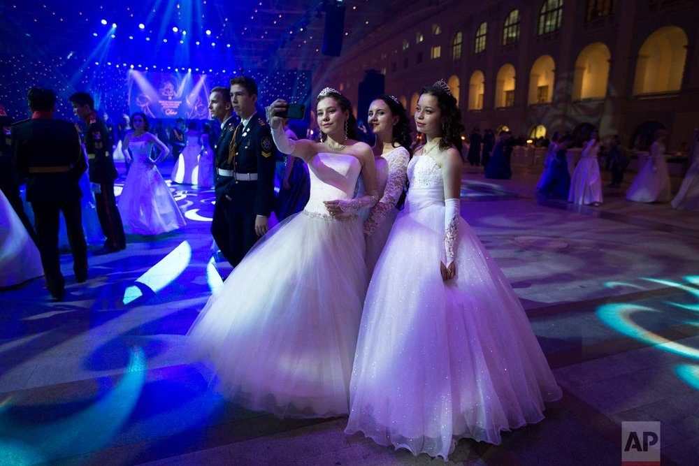 Military school students take selfies during their annual ball in Moscow, Russia, Tuesday, Dec. 12, 2017. (AP Photo/Alexander Zemlianichenko)