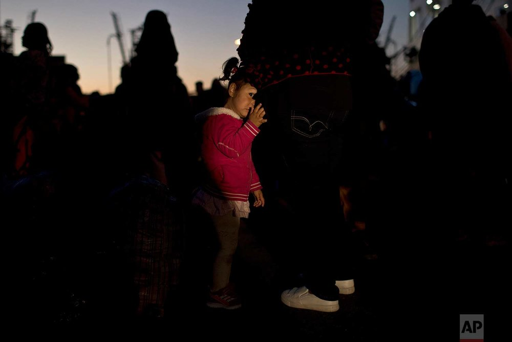 An Afghan child looks on as she leans on her mother after their arrival on a Greek ferry at the port of Piraeus near Athens, early Wednesday, Dec. 13, 2017. (AP Photo/Petros Giannakouris)