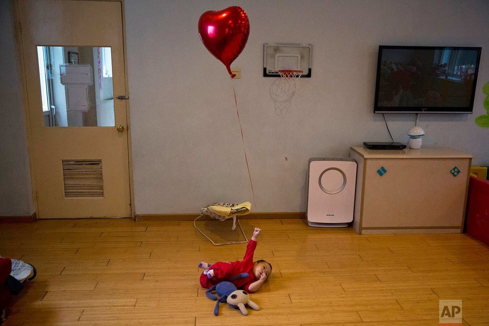 A child plays with a balloon at a foster home of the New Hope Foundation on the outskirts of Beijing, China, on Wednesday, Oct. 11, 2017. (AP Photo/Ng Han Guan)