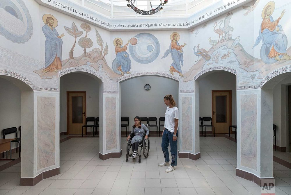 Tutor Valeria and 11-year-old pupil Feruza cross through a chapel at the St. Sophia orphanage in Moscow, Russia, on Tuesday, Sept. 12, 2017. (AP Photo/Ivan Sekretarev)