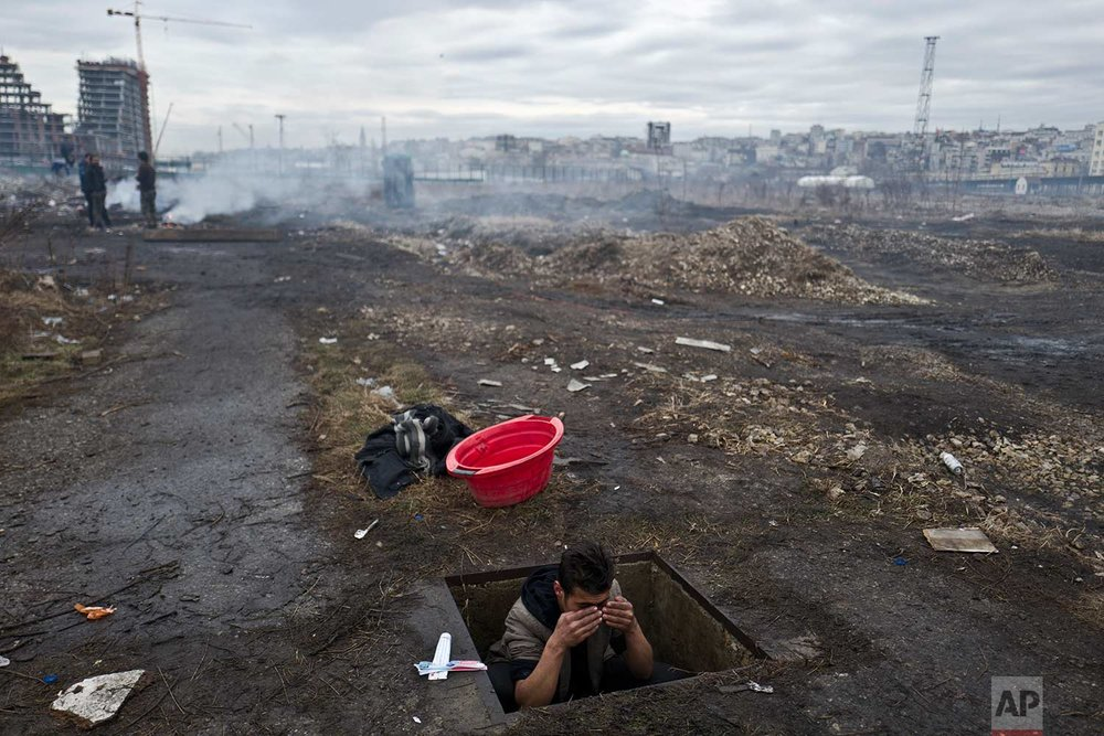 In this Thursday, Feb. 2, 2017 photo, an Afghan refugee youth washes himself in a hole in the ground outside an old train carriage where he and other migrants took refuge in Belgrade, Serbia. Hundreds of migrants have been sleeping rough in freezing conditions in central Belgrade looking for ways to cross the heavily guarded EU borders. (AP Photo/Muhammed Muheisen)