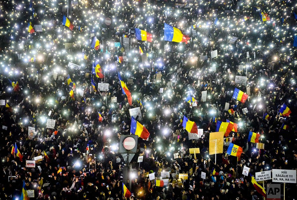 In this Sunday, Feb. 5, 2017 photo, tens of thousands of people shine lights from mobile phones and torches during a protest in front of the government building in Bucharest, Romania. Romania's government met Sunday to repeal an emergency decree that decriminalizes official misconduct, a law that has prompted massive protests at home and widespread condemnation from abroad. (AP Photo/Andreea Alexandru)