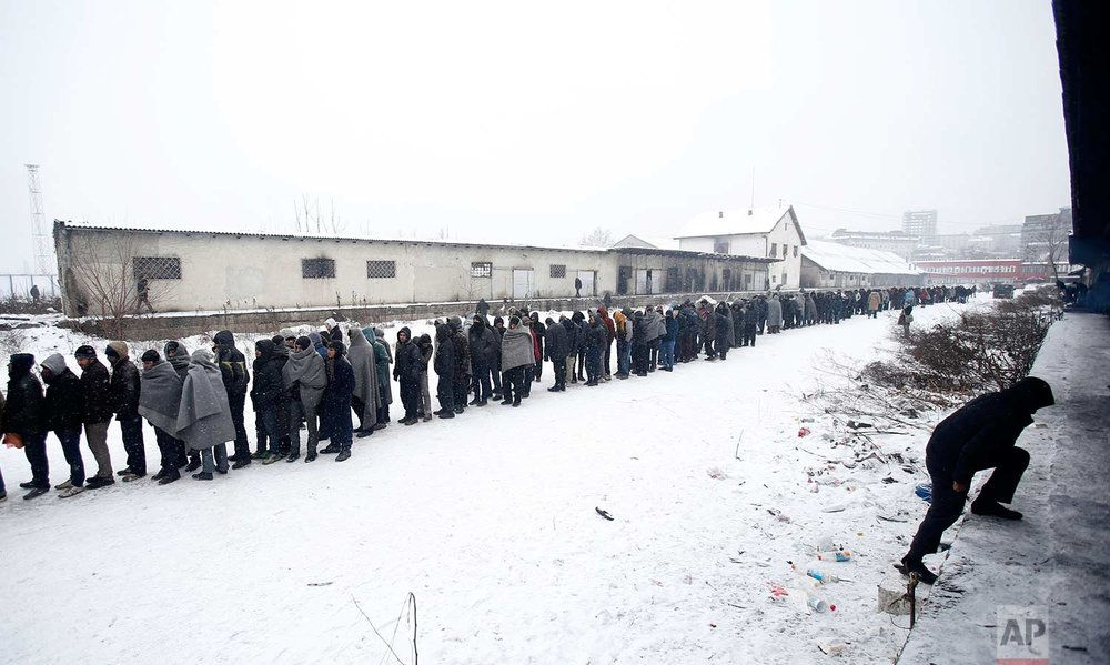 In this Tuesday, Jan. 10, 2017 photo, migrants queue for food in front of an abandoned warehouse in Belgrade, Serbia. Hundreds of migrants are sleeping rough in parks and make-shift shelters in the Serbian capital in freezing temperatures waiting for a chance to move forward toward the European Union. (AP Photo/Darko Vojinovic)