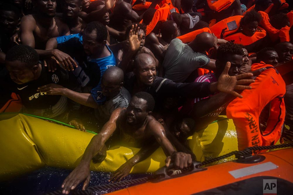 In this Tuesday, July 25, 2017 photo, sub-Saharan migrants receive life jackets as they are rescued by aid workers of Spanish NGO Proactiva Open Arms in the Mediterranean Sea, about 15 miles north of Sabratha, Libya. (AP Photo/Santi Palacios)