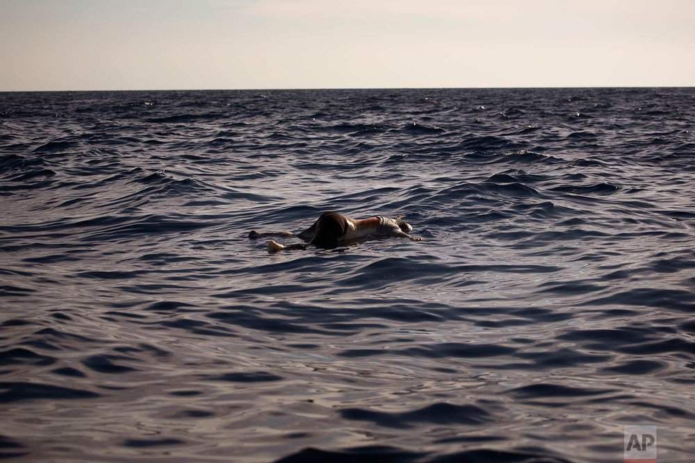 In this Wednesday, June 21, 2017 photo, a dead body of a woman is seen floating on the mediterranean sea, at 20 miles north of Zuwarah, Libya. At least three bodies with sign of decompositions were found by aid organisations on Wednesday, apparently from a recent sinking boat in the area from people who were attempting the perilous crossing of the Mediterranean Sea to Europe in packed boats from Libya. (AP Photo/Emilio Morenatti)