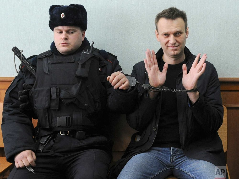 In this Thursday, March 30, 2017 photo, Russian opposition leader Alexei Navalny, right, poses for press in court in Moscow, Russia. Navalny attends a court hearing on his appeal. Navalny, who organized a wave of nationwide protests against government corruption was sentenced to 15 days in jail. (AP Photo)