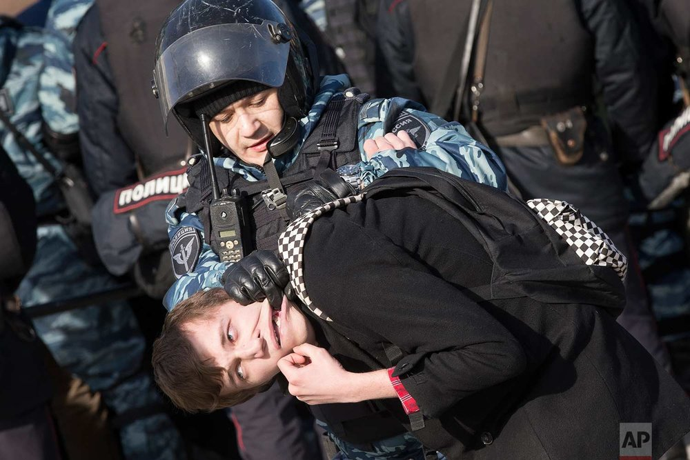 In this Sunday, March 26, 2017 photo, police detain a protester in downtown Moscow, Russia. Thousands of people crowded into Moscow's Pushkin Square on Sunday for an unsanctioned protest against the Russian government, the biggest gathering in a wave of nationwide protests that were the most extensive show of defiance in years. (AP Photo/Alexander Zemlianichenko)