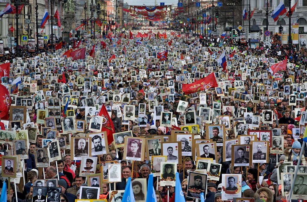 In this Tuesday, May 9, 2017 photo, local residents carry portraits of their ancestors, participants in World War II as they celebrate the 72nd anniversary of the defeat of the Nazis in World War II in St. Petersburg, Russia. About 400,000 people walked in central streets of St. Petersburg in a march named 'Immortal Regiment' while carrying portraits of their relatives who fought in World War II. (AP Photo/Dmitri Lovetsky)