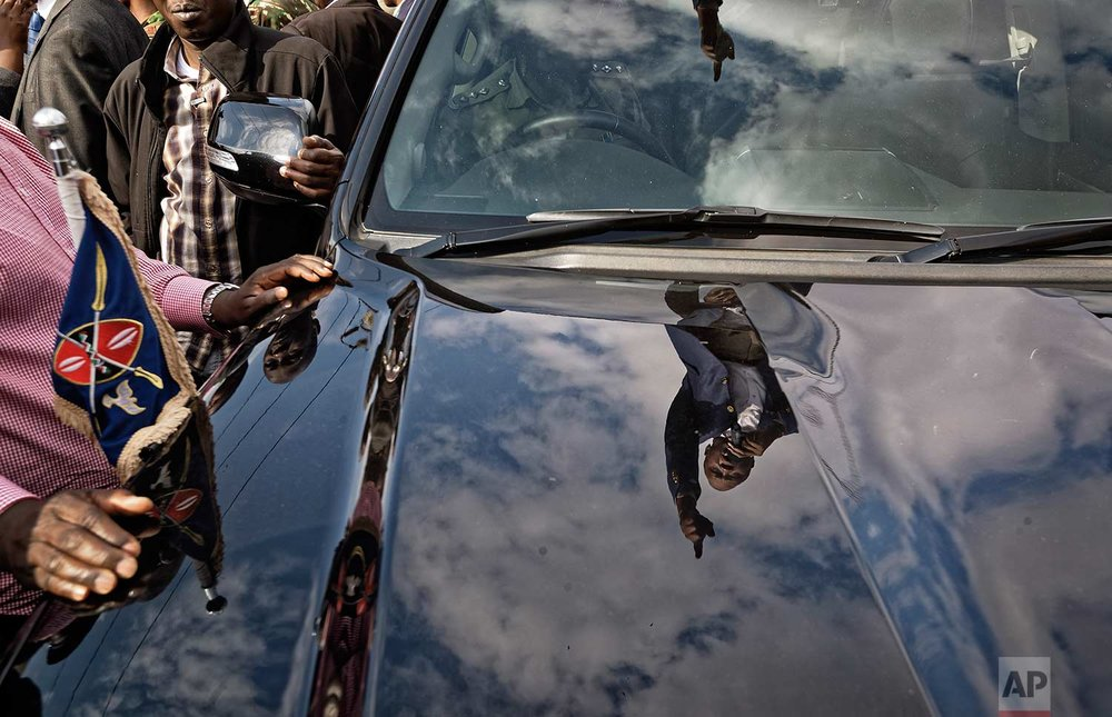 In this Tuesday, Sept. 5, 2017 photo, Kenya's President Uhuru Kenyatta is  reflected in the hood of the presidential vehicle in which he is standing, addresses his supporters on a street in Ongata Rongai, on the outskirts of Nairobi, Kenya. (AP Photo/Ben Curtis)