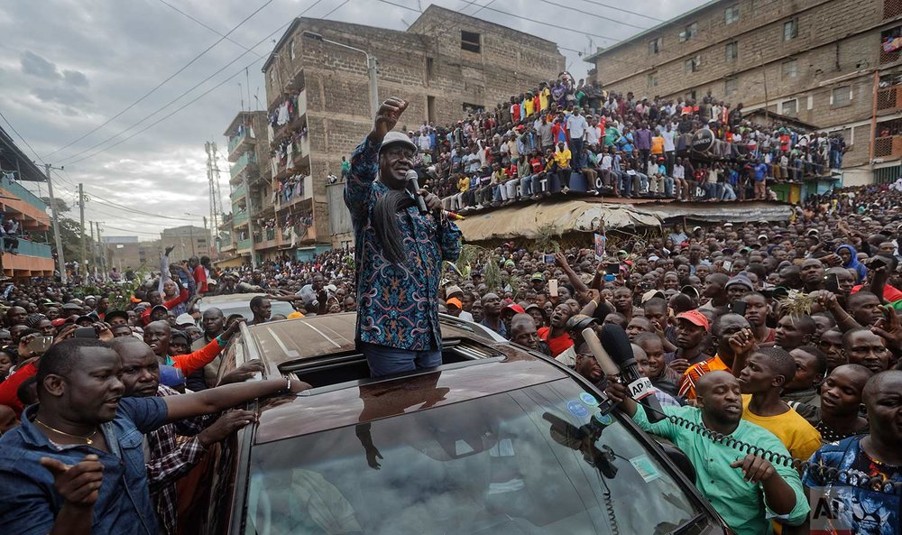 In this Sunday, Aug. 13, 2017 photo, Kenyan opposition leader Raila Odinga gestures to thousands of supporters gathered in the Mathare slum of Nairobi, Kenya. Odinga on Sunday condemned police killings of rioters during protests after the country's disputed election and is urging supporters to skip work Monday. (AP Photo/Ben Curtis)