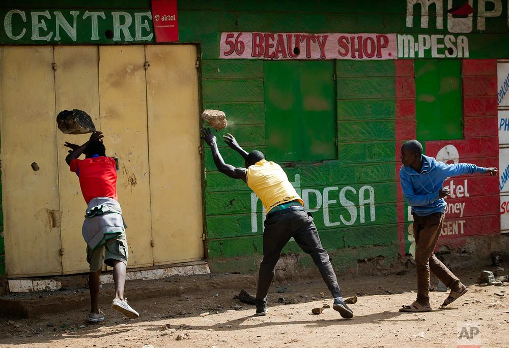 In this Saturday, Oct. 28, 2017 photo, opposition supporters attempt to break the door of a shop in order to loot it, in the slum of Kawangware in Nairobi, Kenya. Kenyan opposition areas were calmer Saturday, a day after the country's election commission postponed voting in four restive counties where deadly clashes between police and protesters have occurred.(AP Photo/Darko Bandic)