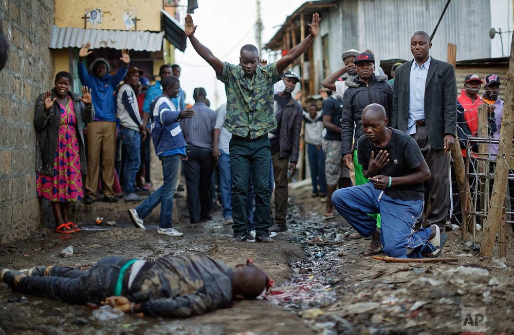 In this Wednesday, Aug. 9, 2017 photo, residents hold their hands up in the air towards police, as a man genuflects, right, next to the body of a man who had been shot in the head and who the crowd claimed had been shot by police, in the Mathare slum of Nairobi, Kenya. Kenya's election took an ominous turn on Wednesday as violent protests erupted in the capital. (AP Photo/Ben Curtis)