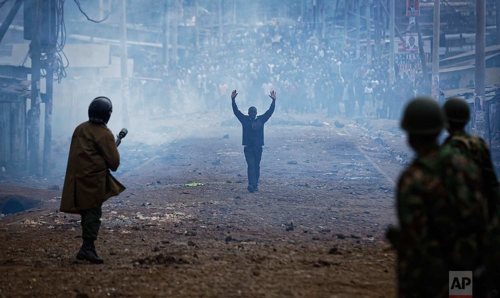 In this Thursday, Aug. 10, 2017 photo, a man seeking safety walks with his hands in the air through a thick cloud of tear gas towards riot police, as they clash with protesters throwing rocks in the Kawangware slum of Nairobi, Kenya. International observers on Thursday urged Kenyans to be patient as they awaited final election results following opposition allegations of vote-rigging, but clashes between police and protesters again erupted in Nairobi. (AP Photo/Ben Curtis)