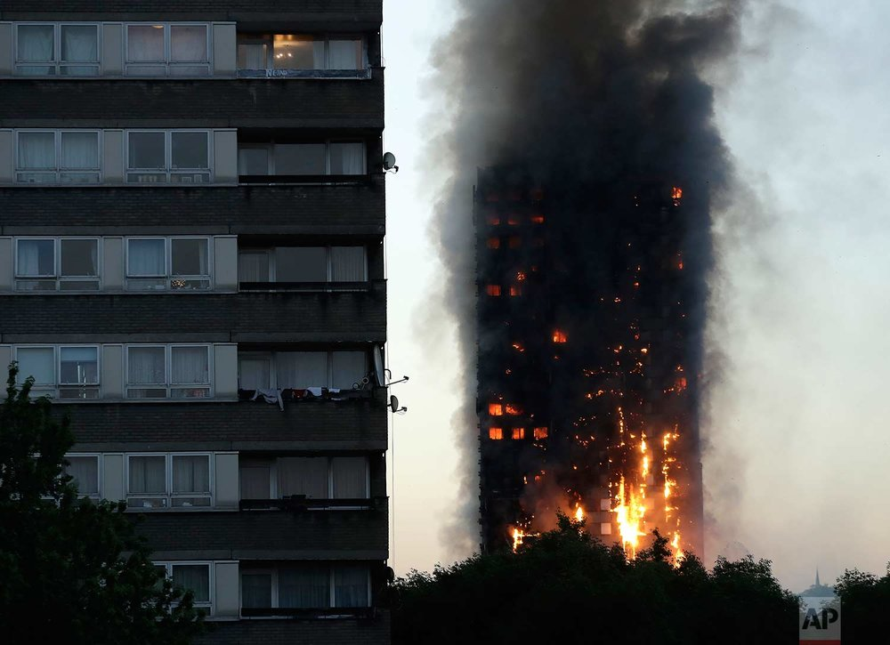 In this Wednesday, June 14, 2017 photo, smoke and flames rise from the Grenfell Tower high-rise building in west London. (AP Photo/Matt Dunham)