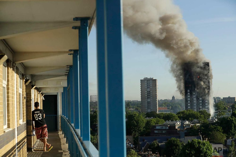 In this Wednesday, June 14, 2017 photo, a resident in a nearby high-rise building watches smoke rise from a massive fire at the high-rise Grenfell Tower in London. (AP Photo/Matt Dunham)