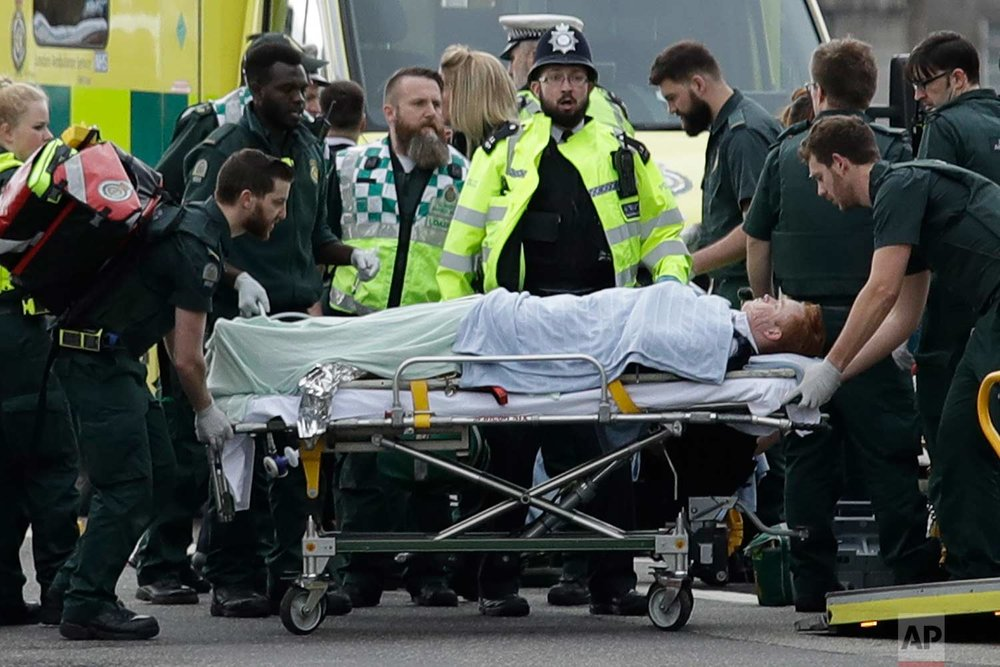 In this Wednesday, March 22, 2017 photo, emergency services staff provide medical attention to injured people on Westminster Bridge, near the Houses of Parliament in London. The Islamic State group claimed responsibility for the attack by a man who plowed an SUV into pedestrians on the bridge and then stabbed a police officer to death on the grounds of Britain's Parliament. (AP Photo/Matt Dunham)