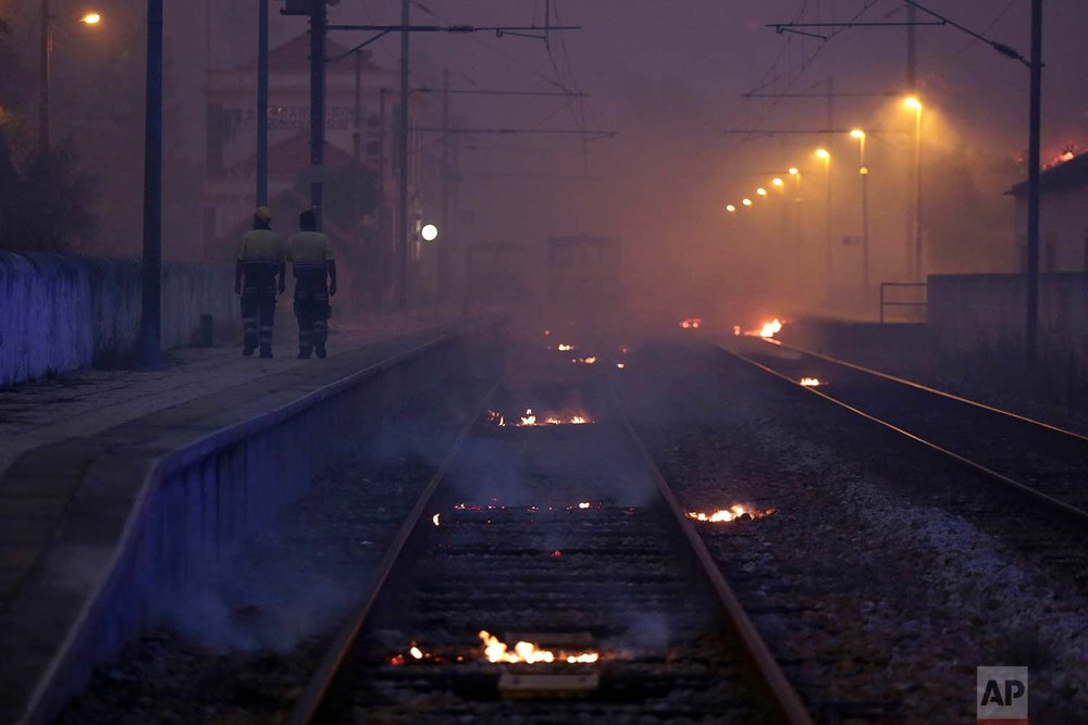In this Wednesday, July 26 2017 photo, railroad ties burn at the Barca da Amieira-Envendos train station outside the village of Sao Jose das Matas, near Macao, central Portugal. More than 2,300 firefighters with over 700 vehicles are tackling wildfires in Portugal, where large areas of woodland are scorched in the summers.  (AP Photo/Armando Franca)