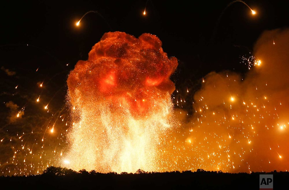 In this Wednesday, Sept. 27, 2017 photo, a powerful explosion is seen in the ammunition depot at a military base in Kalynivka, west of Kiev, Ukraine.  Ukrainian officials say they have evacuated more than 30,000 people after a fire and ammunition explosions, at the military base. (AP Photo/Efrem Lukatsky)