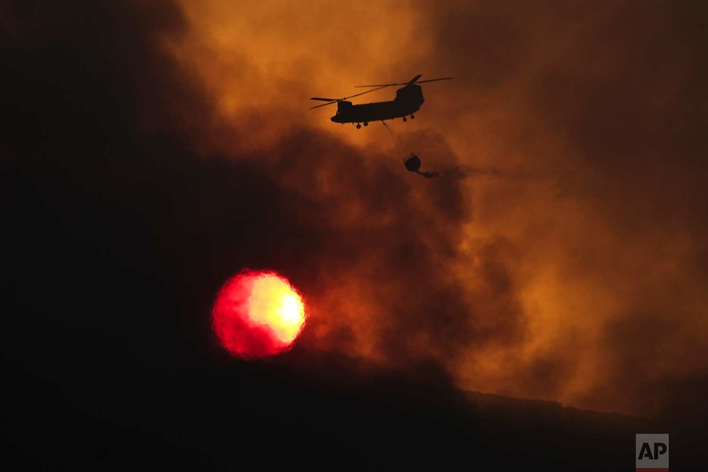 In this Tuesday Aug. 15, 2017 photo, a fire fighting helicopter flies amid smoke as the sun sets during a forest fire near Kapandriti  north of Athens. A large wildfire north of Athens is threatening homes as it sweeps through pine forest for a third day, uncontained due to high winds.(AP Photo/Petros Giannakouris)