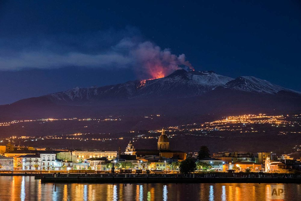 In this Tuesday, April 11, 2017 photo, Mount Etna, Europe's most active volcano, spews lava as the Sicilian town of Riposto, Italy, is visible in foreground, during an eruption. (AP Photo/Salvatore Allegra)