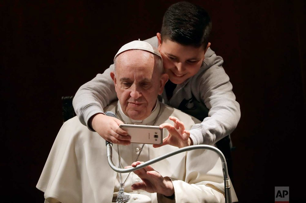 In this Sunday, Feb. 19, 2017 photo, a boy takes a selfie with Pope Francis, during a visit to the parish of Santa Maria Josefa del Cuore di Gesu', in Rome. (AP Photo/Alessandra Tarantino)