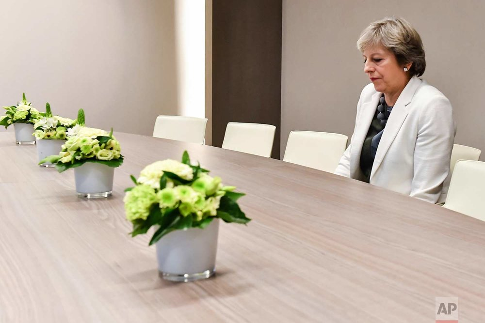 In this Friday, Oct. 20, 2017 photo, British Prime Minister Theresa May waits for the arrival of European Council President Donald Tusk prior to a bilateral meeting with European Council President Donald Tusk during an EU summit in Brussels. European Union leaders gathered Friday to weigh progress in negotiations on Britain's departure from their club as they look for new ways to speed up the painfully slow moving process. (AP Photo/Geert Vanden Wijngaert)