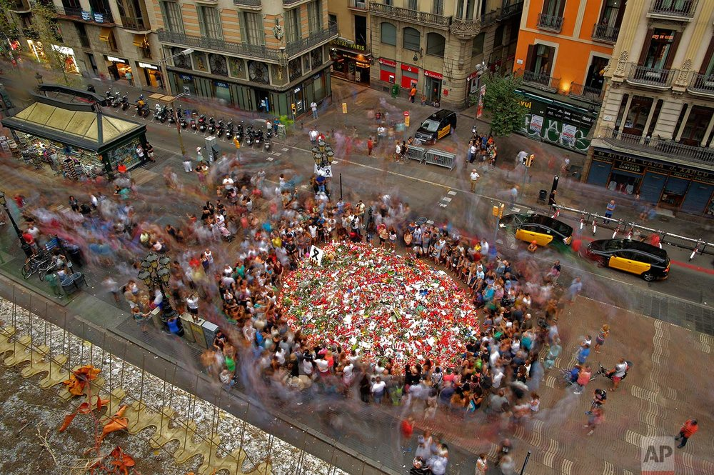 In this Saturday, Aug. 19, 2017 photo, people pay respect at a memorial tribute of flowers, messages and candles to the victims on Barcelona's historic Las Ramblas promenade on the Joan Miro mosaic, embedded in the pavement where the van stopped after killing at least 13 people in Barcelona, Spain. (AP Photo/Manu Fernandez)