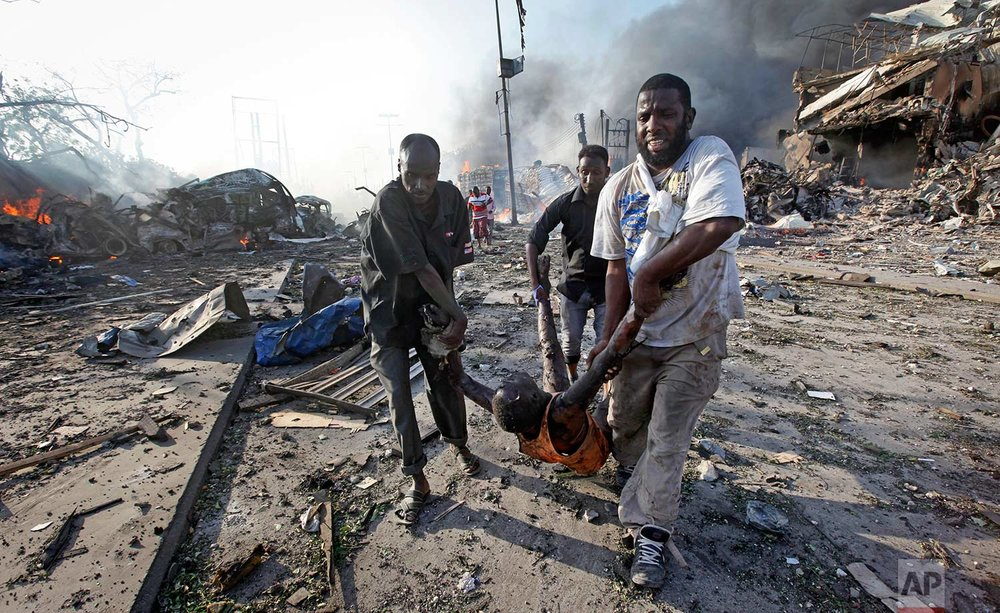 In this Saturday, Oct. 14, 2017 photo, Somalis remove the body of a man killed in a blast in the capital Mogadishu, Somalia. A huge explosion from a truck bomb has killed at least 20 people in Somalia's capital, police said Saturday, as shaken residents called it the most powerful blast they'd heard in years. (AP Photo/Farah Abdi Warsameh)