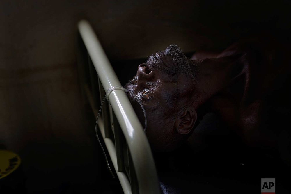 In this Monday, April 3, 2017 photo, Alfred Wani lays on a bed in the clinic at the Imvepi refugee settlement in northern Uganda. Alfred fell ill during the night and had to have blood drawn. (AP Photo/Jerome Delay)