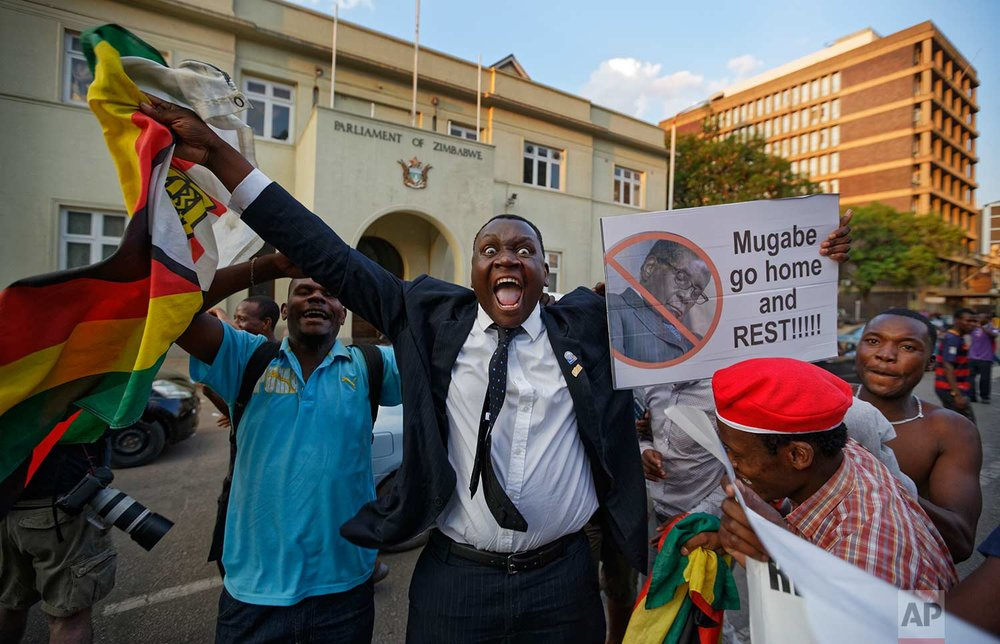 In this Tuesday, Nov. 21, 2017 photo, Zimbabweans celebrate outside the parliament building immediately after hearing the news that President Robert Mugabe had resigned, in downtown Harare, Zimbabwe. Mugabe resigned as president with immediate effect Tuesday after 37 years in power, shortly after parliament began impeachment proceedings against him. (AP Photo/Ben Curtis)