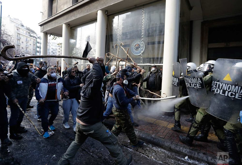 In this Wednesday, March 8, 2017 photo, riot police clash with protesting farmers outside the greek Agriculture Ministry, in Athens. Police fired tear gas to prevent farmers from forcing their way into the ministry building, while protesters responded by throwing stones. No injuries or arrests were reported. Protesters are angry at increases in their tax and social security contributions, part of the income and spending cuts Greece's left-led government has implemented to meet bailout creditor-demanded budget targets.(AP Photo/Thanassis Stavrakis)