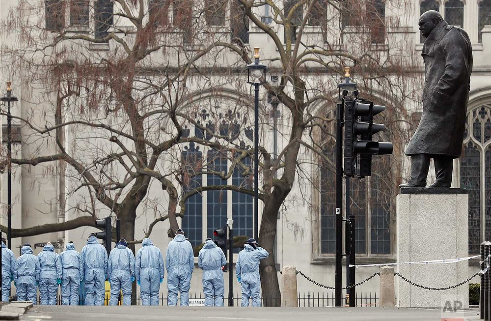 In this Thursday March 23, 2017 photo, police forensic officers work in Parliament Square overseen by the statue of Winston Churchill outside the Houses of Parliament in London. On Wednesday a knife-wielding man went on a deadly rampage, first driving a car into pedestrians then stabbing a police officer to death before being fatally shot by police within Parliament's grounds in London. (AP Photo/Kirsty Wigglesworth)
