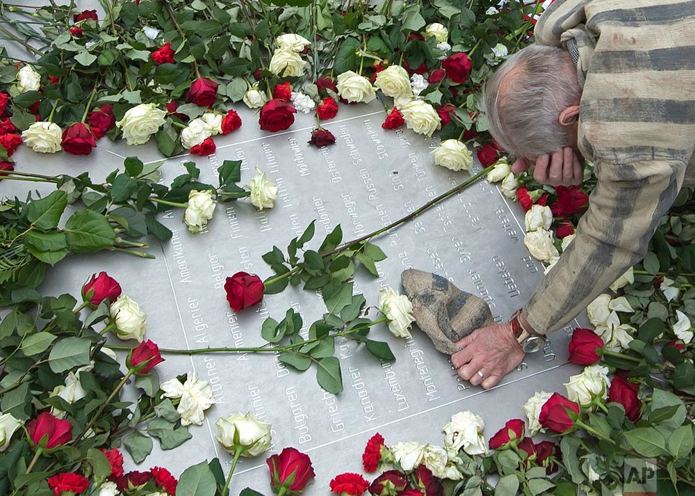 In this Tuesday, April 11, 2017 photo, Nazi concentration camp survivor Alexander Bytschok of Kiev, Ukraine, mourns on a metal plaque during the commemoration ceremonies for the 72th anniversary of the liberation of the former Nazi concentration camp Buchenwald near Weimar, Germany. (AP Photo/Jens Meyer)