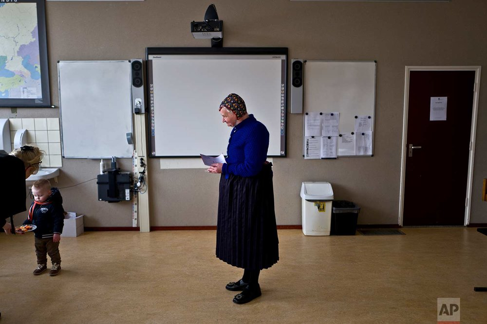 In this Wednesday, March 15, 2017 photo, an elderly woman wearing a traditional hat waits her turn to cast her vote for the Dutch general elections at a polling station in a school in Staphorst, Netherlands. Mark Rutte, the Dutch prime minister who had pushed the electorate through five years of tough economic measures, emerged victorious in a bruising battle with Geert Wilders, whose relentless invective against all things Muslim and anything from the European Union failed to earn him the breakthrough that many had come to count on as a given. (AP Photo/Muhammed Muheisen)