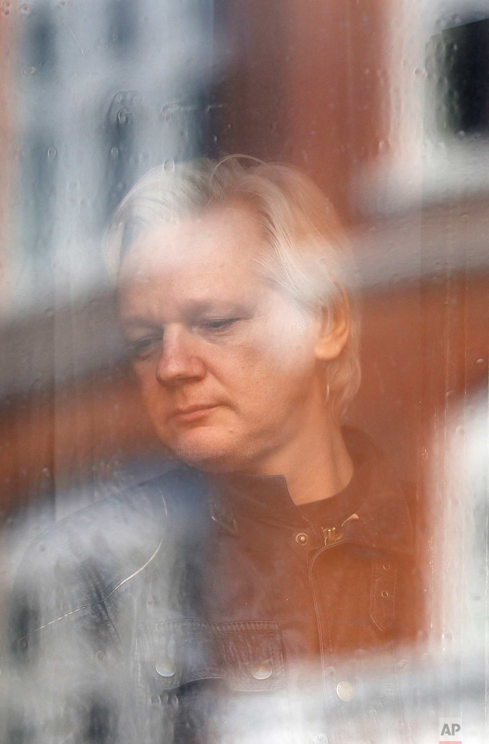 In this Friday May 19, 2017 photo, Julian Assange looks out the window from the Ecuadorian embassy in London. Sweden's top prosecutor says she is dropping an investigation into a rape claim against WikiLeaks founder Julian Assange after almost seven years. Assange took refuge in Ecuador's embassy in London in 2012 to escape extradition to Sweden to answer questions about sex-crime allegations from two women. (AP Photo/Frank Augstein)