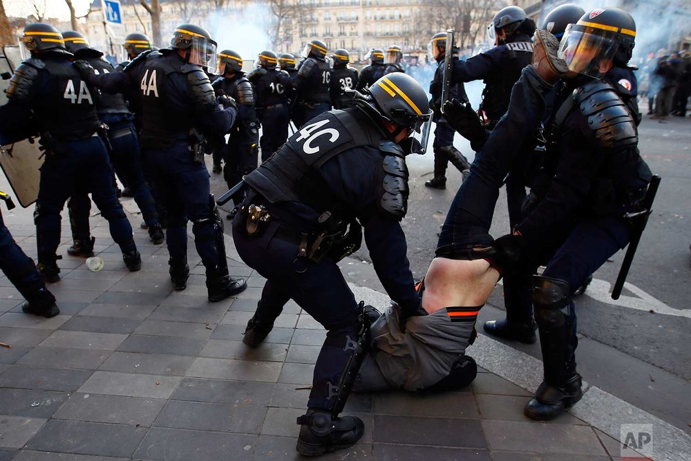 In this Saturday, Feb. 18, 2017 photo, riot Police officers apprehend a protester during clashes at a demonstration against alleged police abuse, in Paris. Anti-racism groups and other activists are gathered in Paris in support of victims of police violence, after a young black man was allegedly raped with a police baton in an incident that prompted violent protests in impoverished suburbs. (AP Photo/Francois Mori)