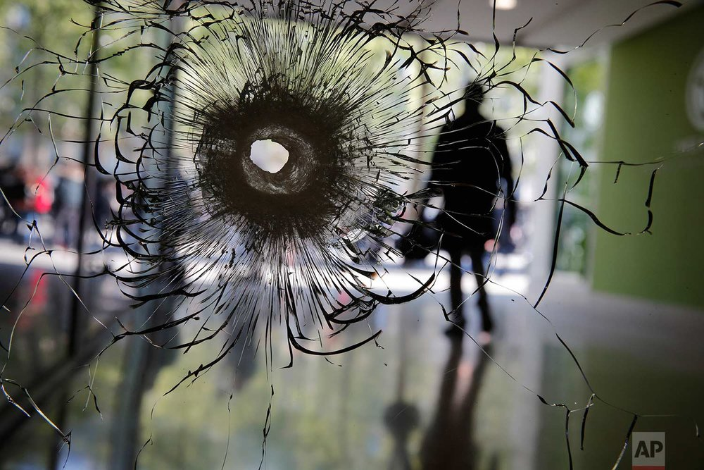 In this Friday, April 21, 2017 photo, a bullet hole is pictured on a shopwindow of the Champs Elysees boulevard in Paris. France began picking itself up Friday from another deadly shooting claimed by the Islamic State group, with President Francois Hollande convening the government's security council and his would-be successors in the presidential election campaign treading carefully before voting this weekend. (AP Photo/Christophe Ena)