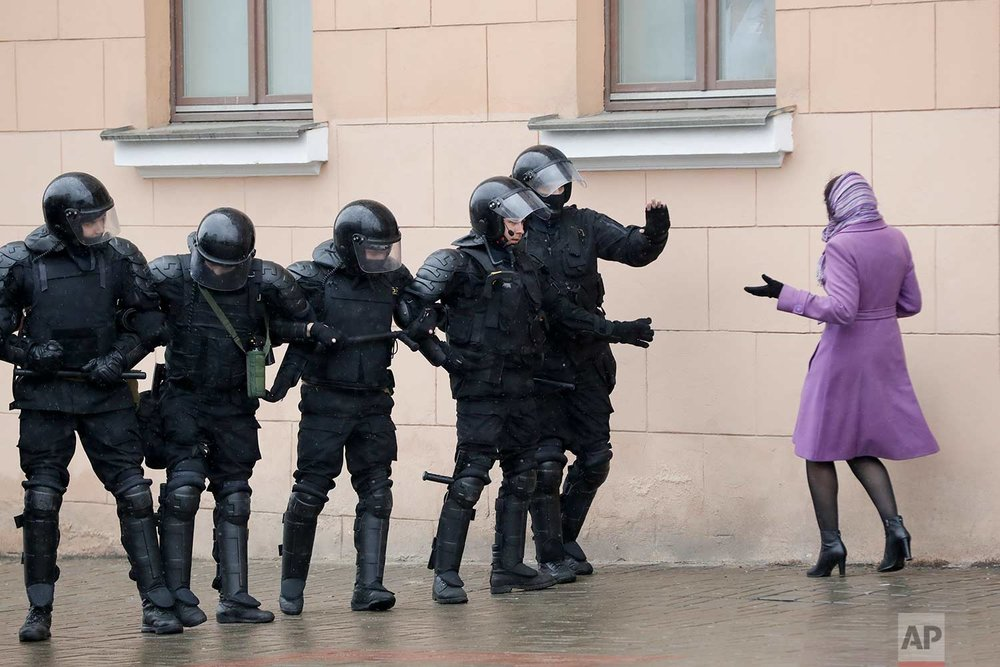In this Saturday, March 25, 2017 photo, a woman argues as Belarus police block a street during an opposition rally in Minsk, Belarus. A cordon of club-wielding police blocked the demonstrators' movement along Minsk's main avenue near the Academy of Science. Hulking police detention trucks were deployed in the city center. (AP Photo/Sergei Grits)